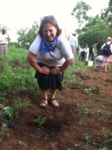 Carol Zuegner bending over small tree sapling in Uganda